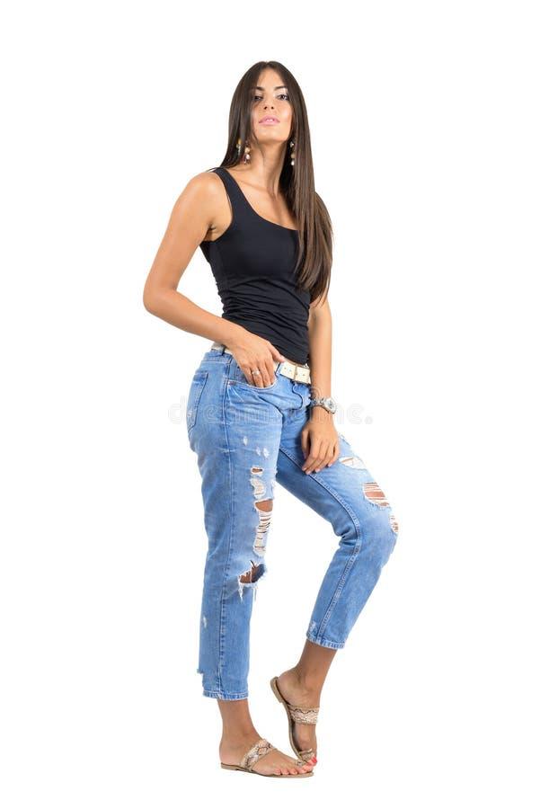Jonge toevallige vrouw in gescheurde jeans die bij camera stellen Het volledige die portret van de lichaamslengte over witte stud royalty-vrije stock fotografie