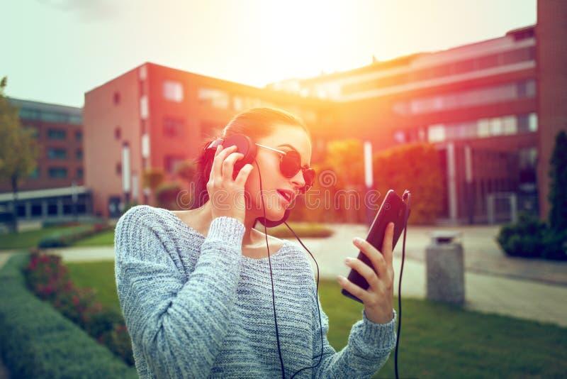 Jonge toevallige vrouw het luisteren muziek door hoofdtelefoons en tablet stock fotografie