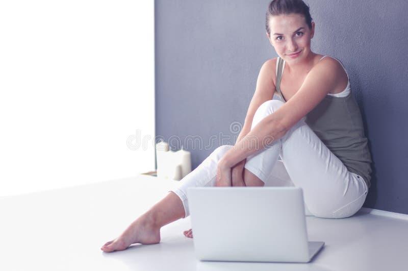 Jonge toevallige vrouwenzitting die neer holdingslaptop glimlachen stock foto