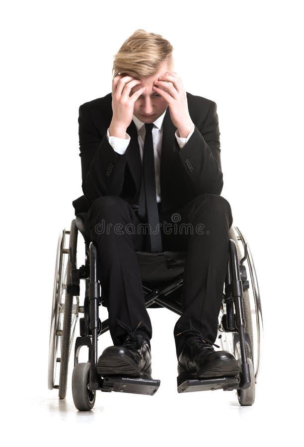 Jonge treurige zakenman in een rolstoel royalty-vrije stock afbeelding