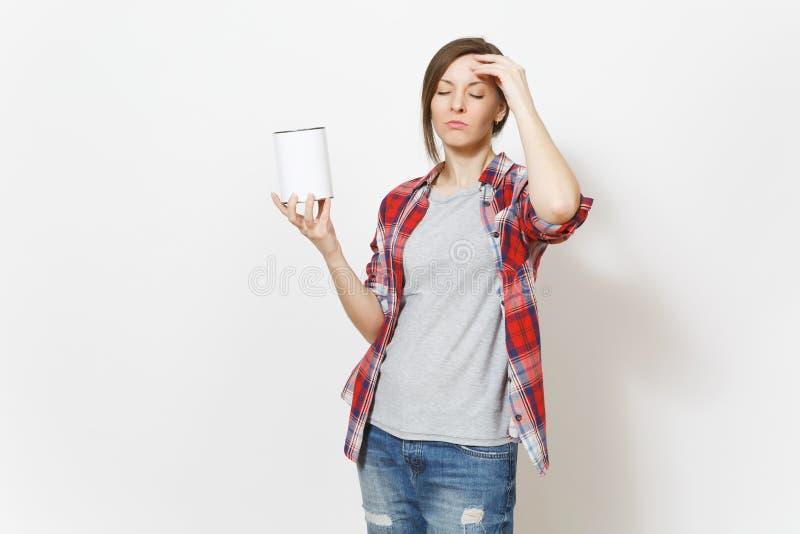 Jonge uitgeputte vrouw die het lege blik van het verftin met exemplaarruimte houden en zich aan hoofd met gesloten geïsoleerde og royalty-vrije stock afbeelding