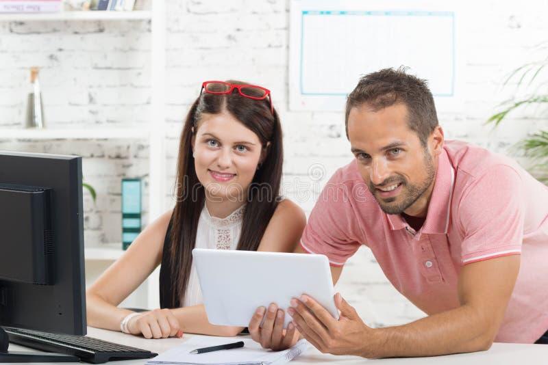Jonge uitvoerend en zijn secretaresse die een tablet bekijken stock afbeeldingen