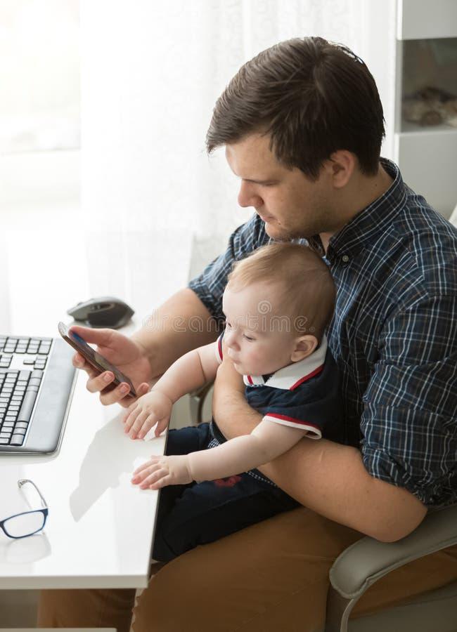 Jonge vader die in bureau werken en babyzoon behandelen royalty-vrije stock afbeeldingen