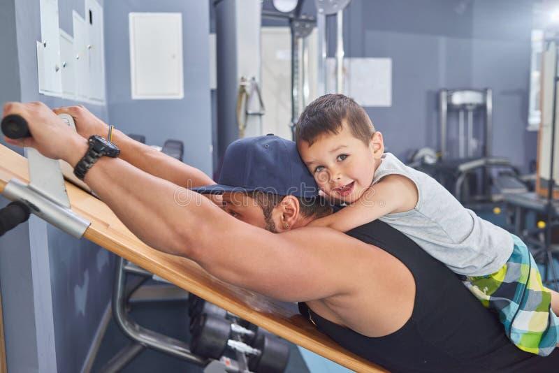 Jonge vader die met sterke spieren in gymnastiek opleiden die weinig zoon op zijn rug houden royalty-vrije stock afbeelding