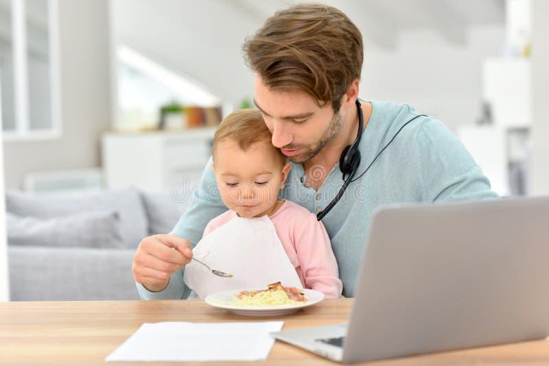 Jonge vader die zijn baby voeden en aan laptop werken stock foto's