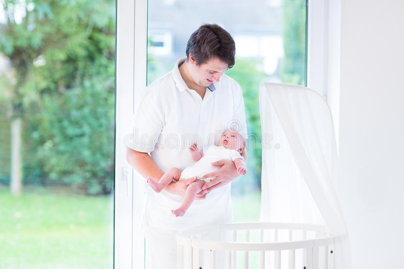 Jonge vader die zijn pasgeboren baby naast voederbak houden royalty-vrije stock afbeeldingen