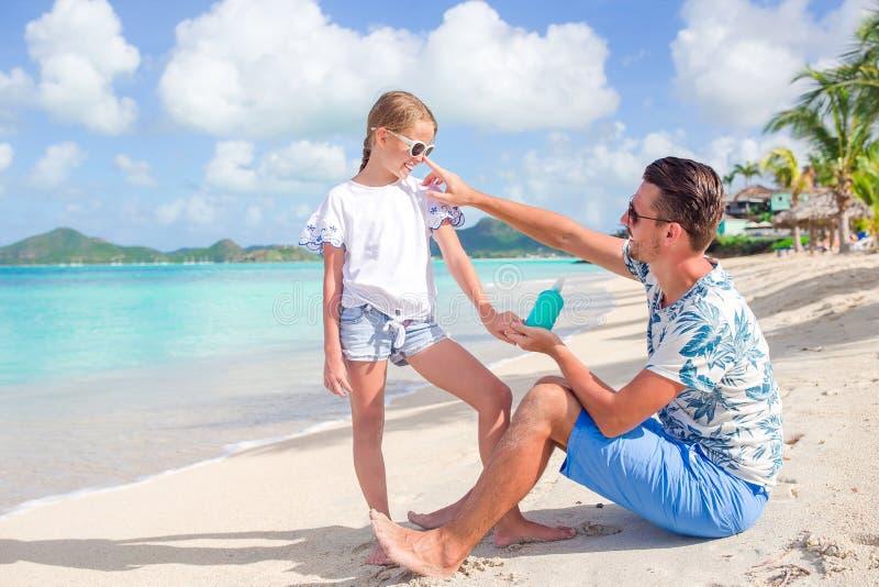 Jonge vader die zonroom toepassen op dochterneus op het strand Vrouw die zonneroom op schouder zetten dichtbij de pool royalty-vrije stock afbeelding