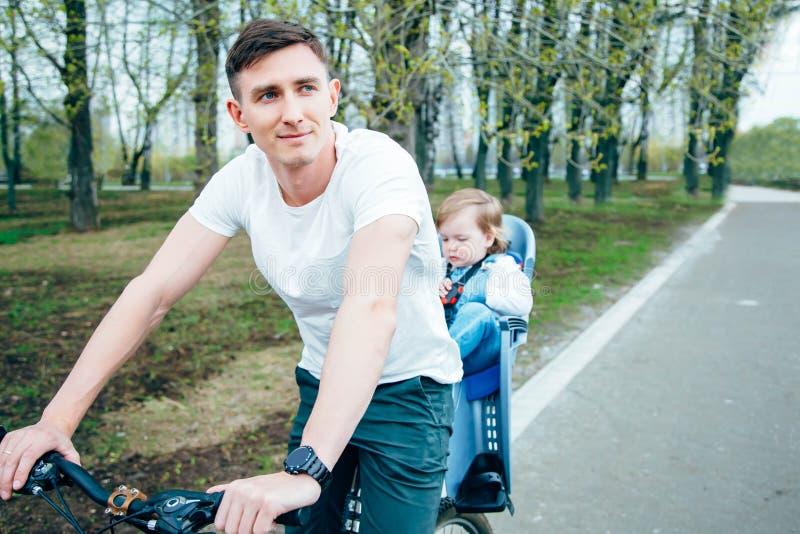 Jonge vader en dochter die een fiets in het park berijden stock afbeelding