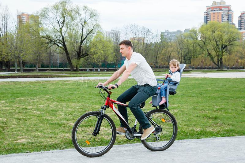 Jonge vader en dochter die een fiets in het park berijden royalty-vrije stock fotografie