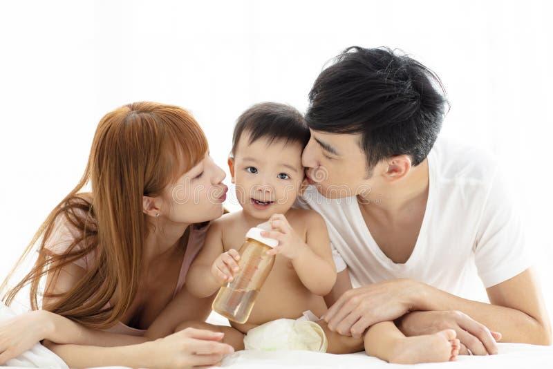 jonge vader en moeder kussende baby stock foto's