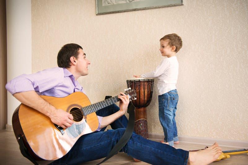 Jonge vader en weinig zoon het spelen gitaar royalty-vrije stock foto's