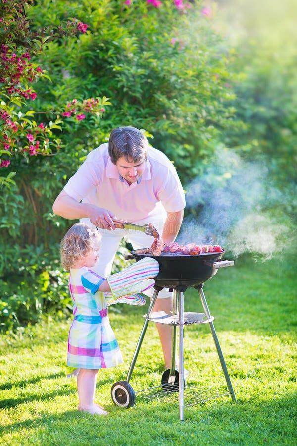 Jonge vader en zijn dochter die in de tuin roosteren royalty-vrije stock afbeeldingen