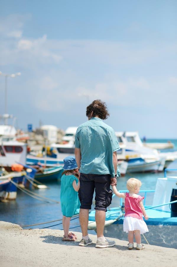 Jonge vader en zijn jonge geitjes bij vissersdorp stock foto