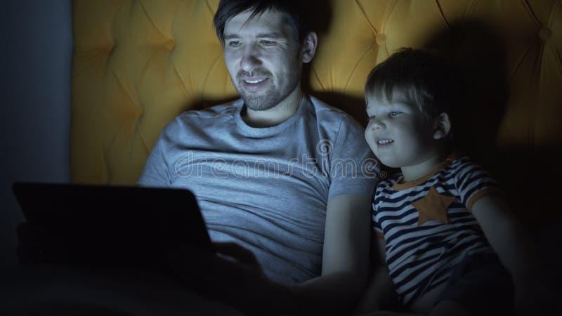 Jonge vader en zijn kleine zoon het letten op beeldverhaalfilm die laptop computer met behulp van terwijl het liggen in bed in th stock fotografie