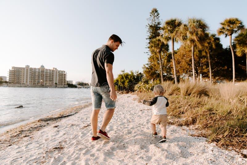 Jonge Vader en Zijn Leuke Little Boy-Zoon die en van het Openluchtweer van Nice op Sandy Beach naast de Oceaanbaai lopen genieten royalty-vrije stock afbeelding