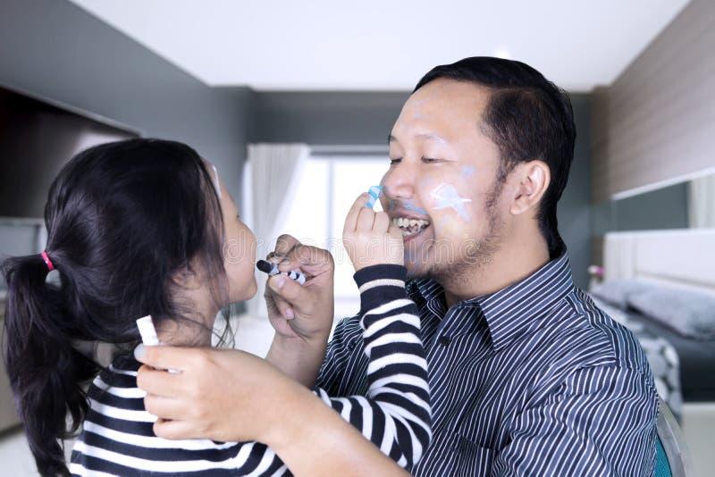 Jonge vader met kind die gezicht het schilderen doen stock fotografie