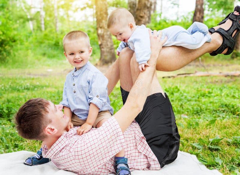 Jonge vader met twee kleine kinderenzonen die pret in het voorste gedeelte hebben stock foto's