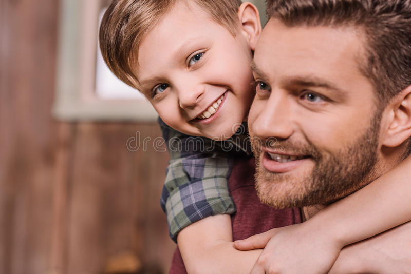 Jonge vader met weinig zoonszitting op portiek bij binnenplaats stock foto