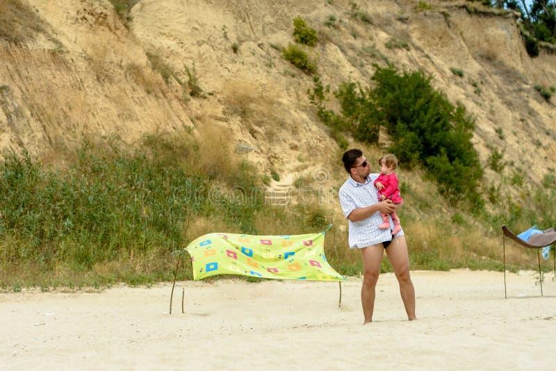 Jonge vader in zonnebril op het strand met een kleine dochter royalty-vrije stock foto