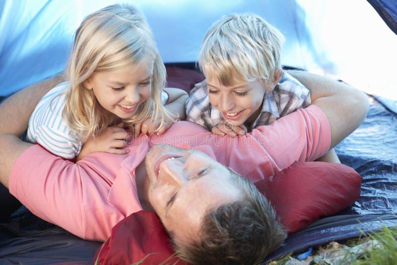 Jonge vaderspelen met kinderen in tent royalty-vrije stock afbeeldingen