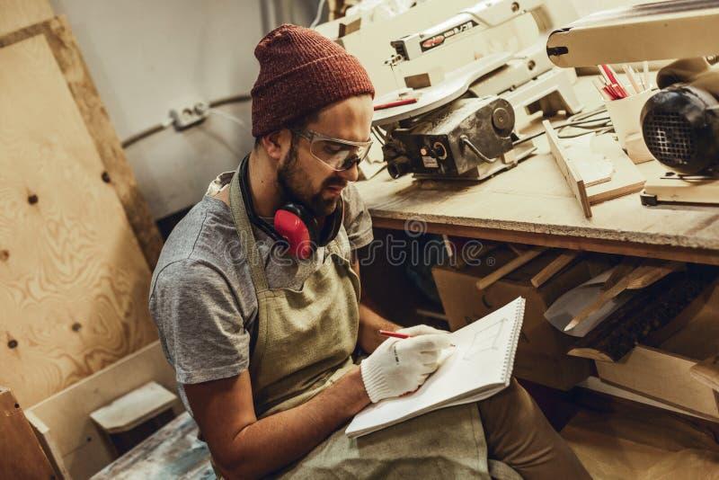 Jonge vakman die in workshop schetsen royalty-vrije stock foto's