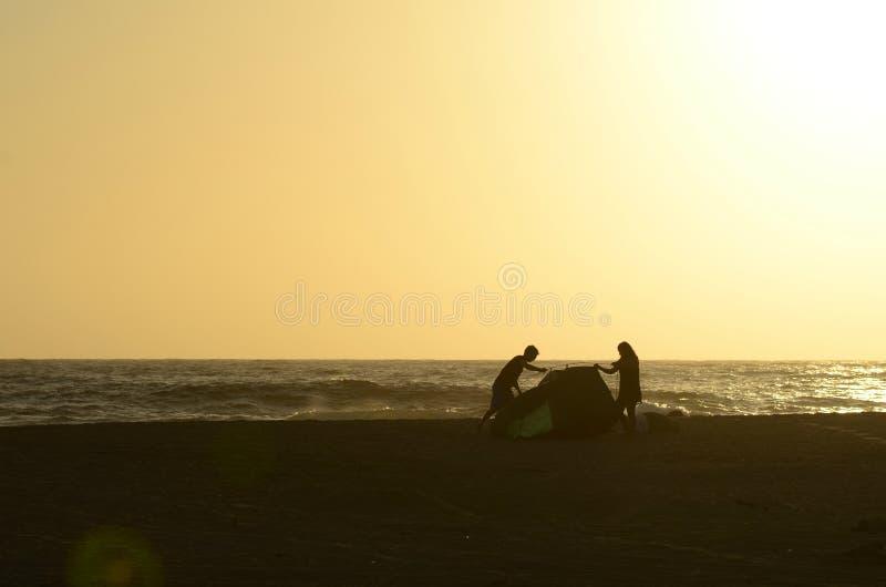 Jonge van de paarman en vrouw silhouetten die tent op tropisch strand opzetten royalty-vrije stock foto