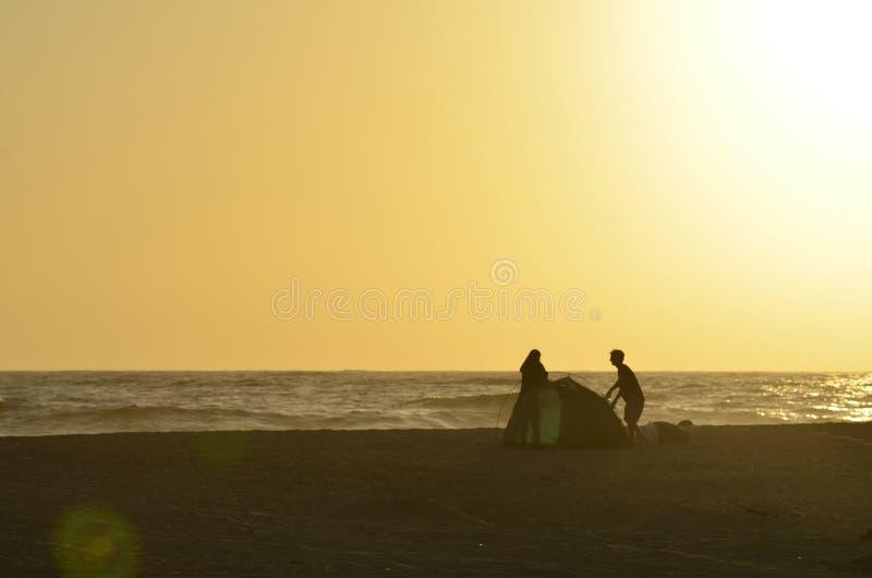 Jonge van de paarman en vrouw silhouetten die tent op tropisch strand opzetten royalty-vrije stock afbeelding