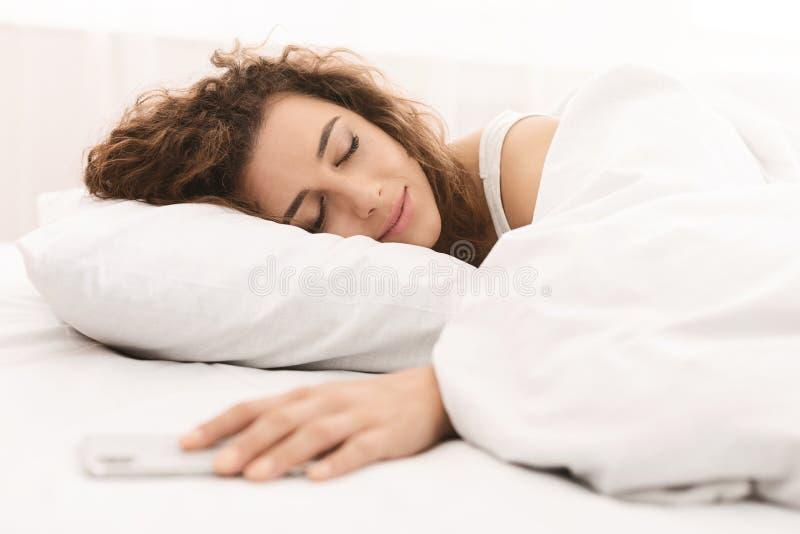 Jonge van de vrouwenslaap en holding smartphone in bed stock foto's