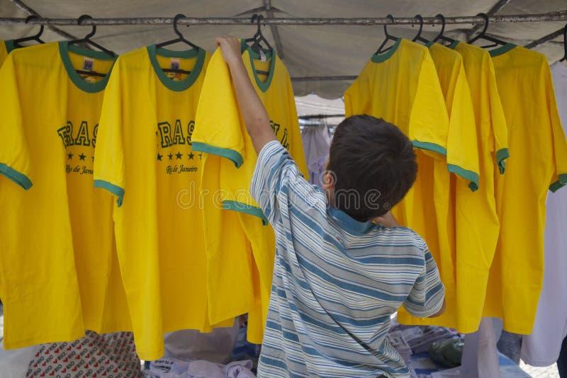 Jonge Verkoper die de Overhemden van Brazilië schikken bij Markt stock afbeeldingen