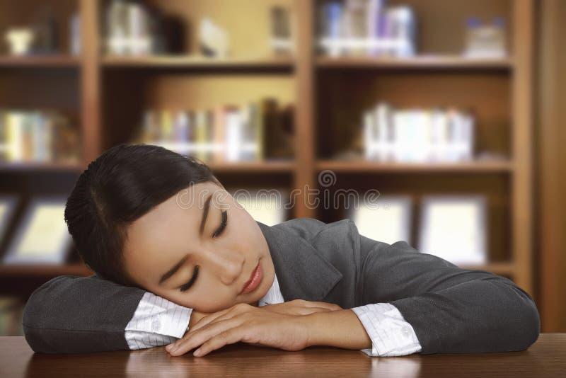 Jonge vermoeide Aziatische vrouwenslaap op bureau stock afbeelding