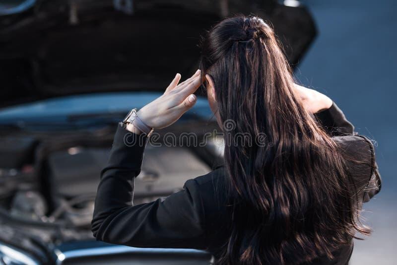 Jonge verontruste vrouw die tempels wrijven terwijl het kijken onder kap van stock foto