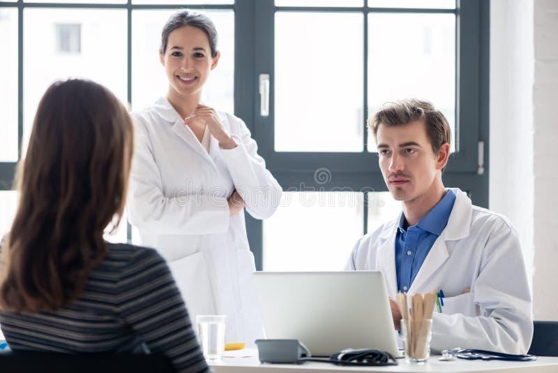 Jonge verpleegster die aan een ervaren arts luisteren terwijl het raadplegen van een patiënt stock foto's