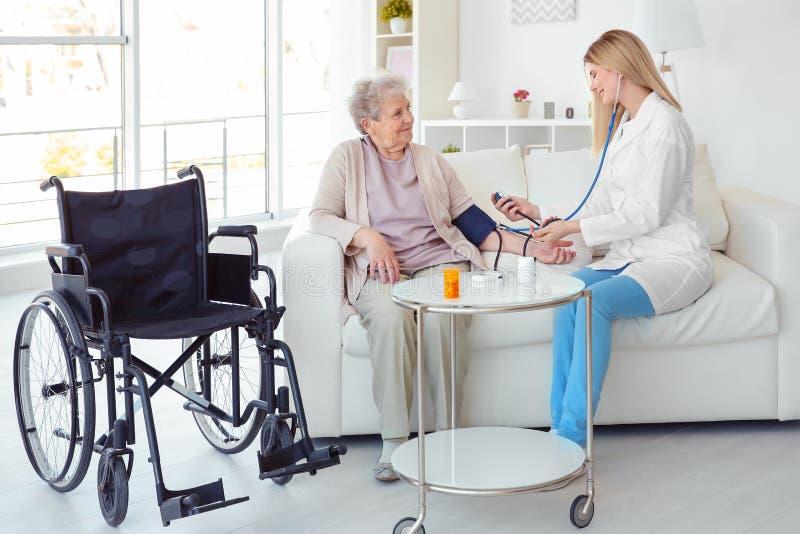 Jonge verpleegster die bloeddruk van gehandicapt bejaarde meten stock foto