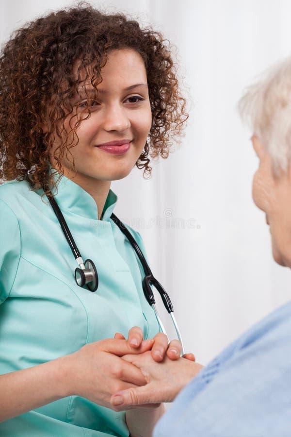 Jonge verpleegster die de hand van een vrouw ouder houden stock afbeeldingen