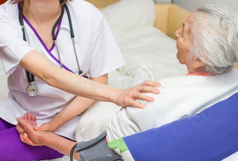 Jonge verpleegster die een oude dame caregiving die in bed liggen royalty-vrije stock foto's