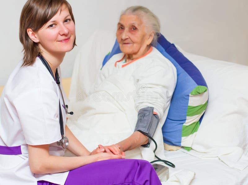 Jonge verpleegster die een oude dame caregiving die in bed liggen stock afbeelding