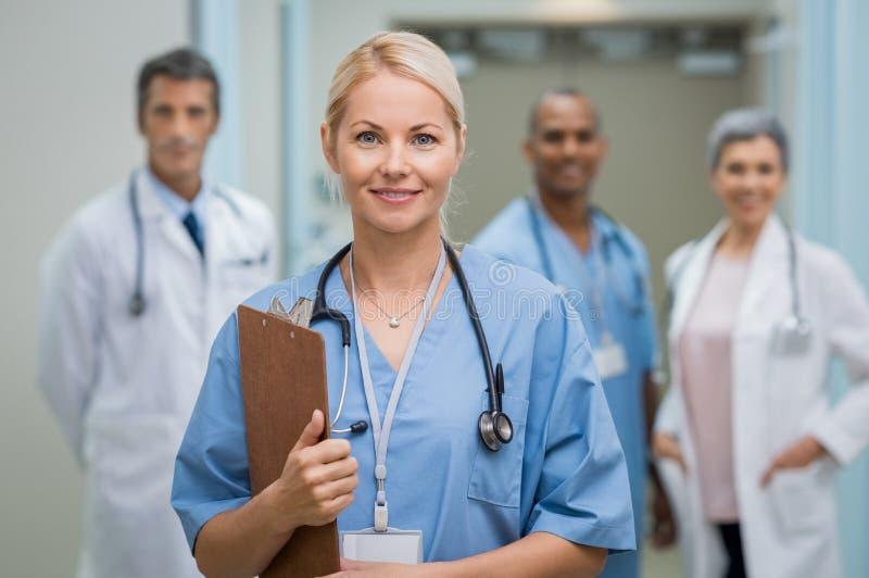 Jonge verpleegster en groepswerk stock foto