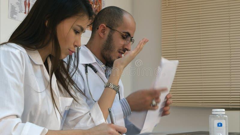 Jonge verpleegster en mannelijke arts die een argument in het bureau hebben stock afbeeldingen