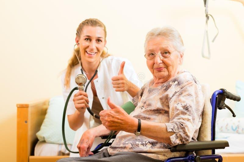 Jonge verpleegster en vrouwelijke oudste in verpleeghuis stock fotografie