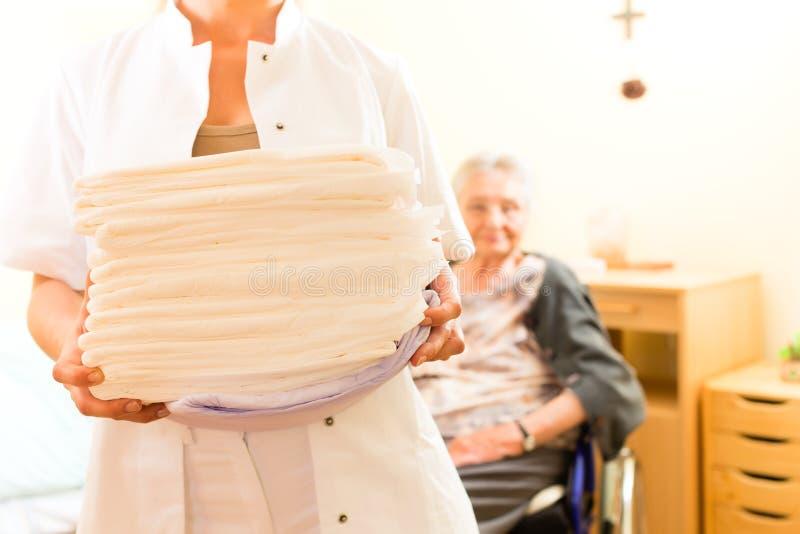 Jonge verpleegster en vrouwelijke oudste in verpleeghuis stock foto