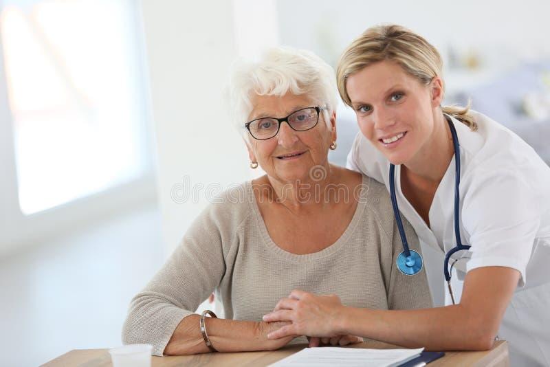 Jonge verpleegster met bejaarde royalty-vrije stock afbeeldingen