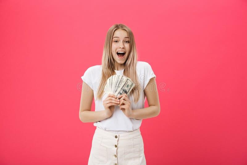 Jonge verraste geschokte studente met geopende die de bundelpartijen van de mondholding van dollars, contant geldgeld op roze wor stock afbeelding
