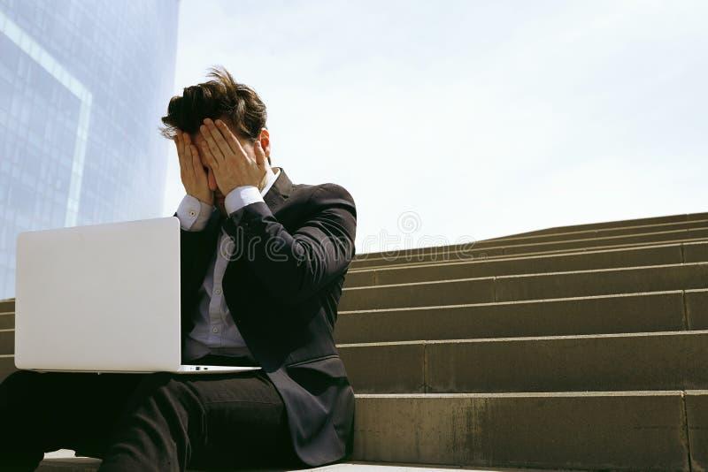 Jonge vertrouwelijke zakenman die kostuum dragen en moderne laptop in openlucht met behulp van Succesvolle bankier die buiten wer stock fotografie