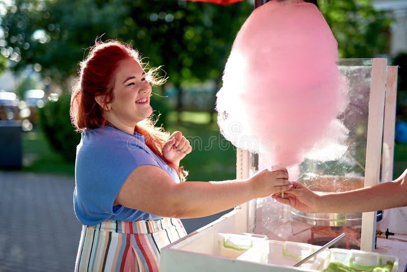 Jonge vette vrouw het kopen gesponnen suiker op stok stock foto