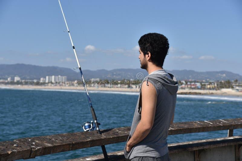 Jonge visser die over de oceaan een tropische toevlucht bekijkt royalty-vrije stock foto