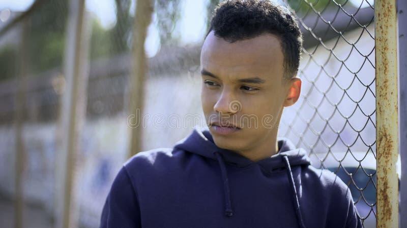 Jonge vluchteling van dysfunctionele familie die op omheining, weestiener leunen royalty-vrije stock afbeeldingen