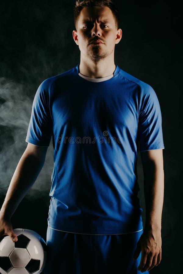 Jonge voetballer met bal op zwarte achtergrond in studio stock foto's