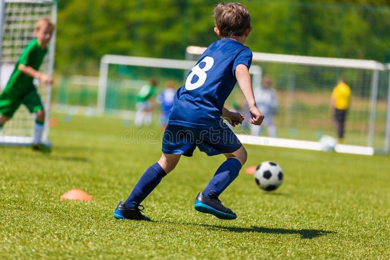 Jonge Voetballers die na de Bal lopen Jonge geitjes in Voetbal Rode en Blauwe Uniformen Voetbalstadion op de Achtergrond royalty-vrije stock afbeeldingen