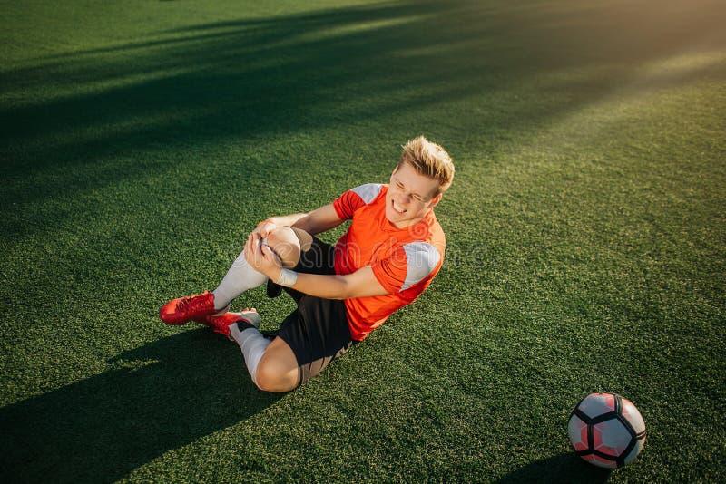 Jonge voetbalster die op groene gazon en greephanden rond been liggen Hij kreeg trauma De kerel voelt vreselijke pijn Hij lijdt stock afbeeldingen