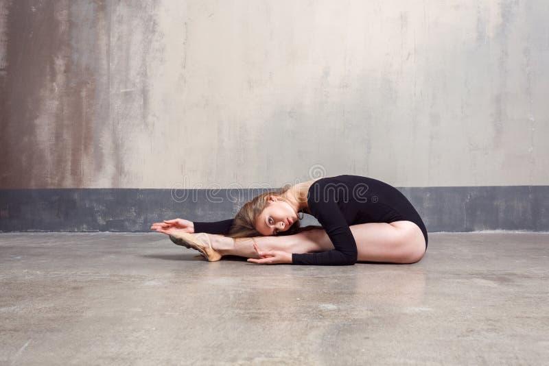 Jonge volwassen balletdanser die oefening uitvoeren terwijl het zitten op F stock afbeeldingen